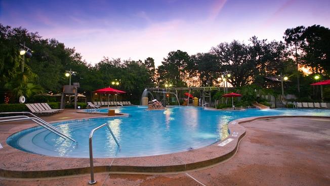 A piscina Ol' Man Island Swimmin' Hole ao pôr do sol, rodeada por espreguiçadeiras e guarda-sóis vermelhos