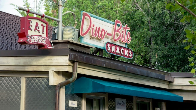 A rustic diner featuring neon lighting and a sign for Dino-Bite Snacks amid trees and other greenery