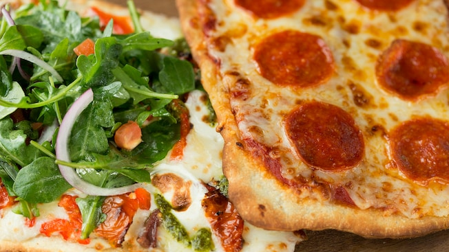 Un pain plat méditerranéen garni d'oignons, de roquette, de tomates rôties, de fromage mozzarella, d'olives Kalamata et de sauce alfredo, à côté d'une tranche de pizza au pepperoni