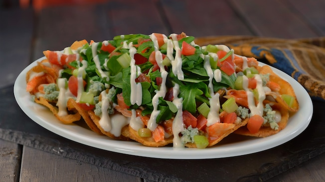 A plate of potato chips topped with shredded chicken, blue cheese, diced tomato, arugula  and ranch dressing
