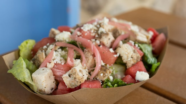 A grilled chicken, feta cheese and watermelon salad sits on a table
