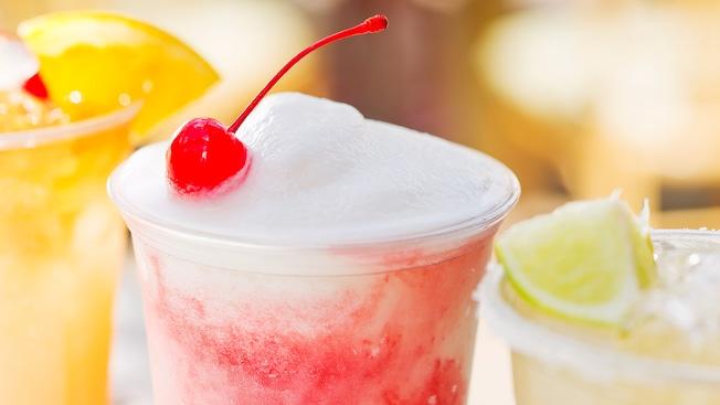 Una bebida cubierta con una rebanada de naranja, una bebida cubierta con una cereza, y una bebida cubierta con una rodaja de limón verde