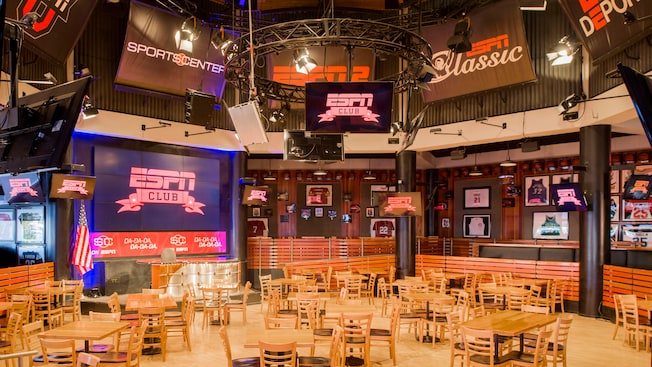 A variety of chairs, tables, flat screen TVs and sports memorabilia fills the ESPN Club dining area