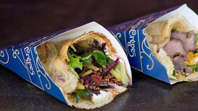 Two crepes served in paper holders, one a vegetarian crepe containing pickled beets, goat cheese, lettuce and candied pecans and the other a beef crepe garnished with shredded cheese and spinach