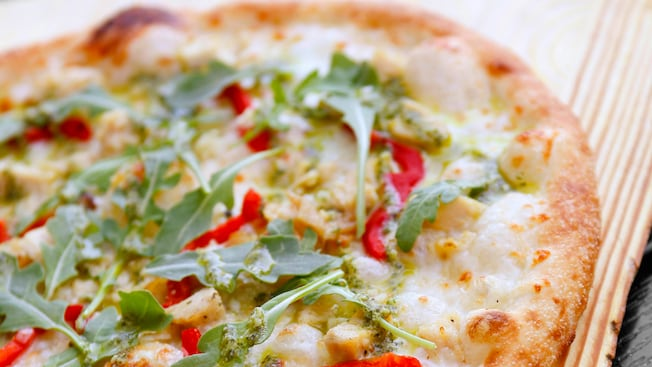 An 11 inch pizza topped with arugula, diced chicken and red peppers
