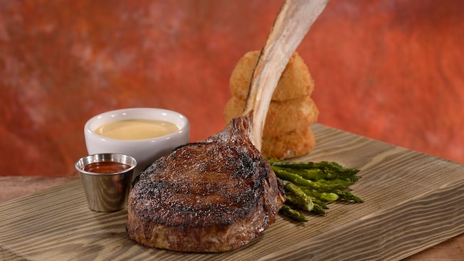 Dry-aged long bone rib chop plated on a wooden cutting board with sauces, onion rings and asparagus