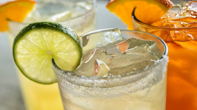 Iced glass of margarita on the rocks with a wedge of lime and other specialty drinks from Dockside Margaritas