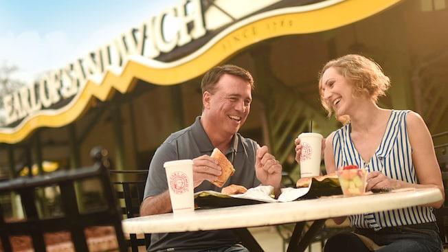 Casal sentado em uma mesa ao ar livre saboreia a refeição do Earl of Sandwich