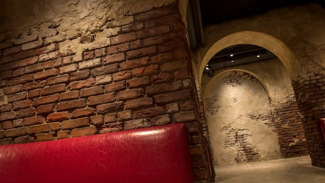 Spackled brick walls and a stone archway inside Enzo's Hideaway