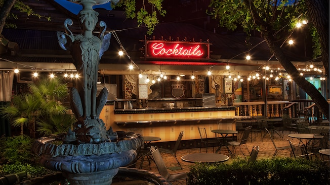 Sphinx-like fountain near patio tables and bar lit up with neon 'Cocktails' sign