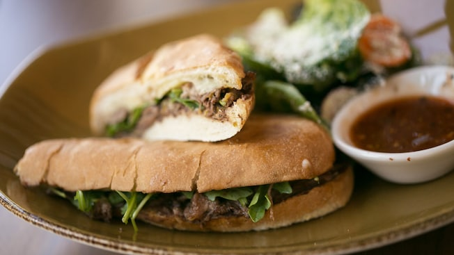 The pepito torta, a slow-cooked short rib sandwich with a small bowl of chipotle salsa and a taqueria salad