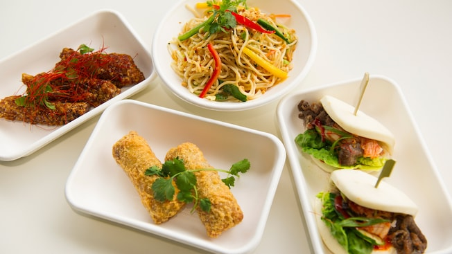 An assortment of Morimoto street food platters including chilled sesame lo mein noodles, kalbi bao, pork egg rolls and takoyaki