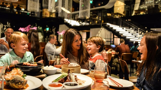 A mother and her 3 children smile while eating in a modern dining room at Morimoto Asia