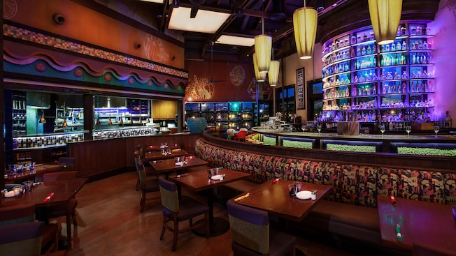 Banquette tables in front of semicircular bar and lit tequila display, across from an open kitchen