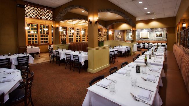 La salle à manger à l'éclairage tamisé du Portobello Country Italian Trattoria avec des chaises et des tables avec couverts
