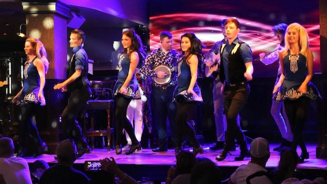 Dançarinos irlandeses se apresentam no palco com uma banda ao vivo