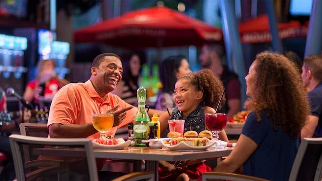 Un padre y su hija pequeña disfrutan comidas y bebidas en el comedor de Splitsville