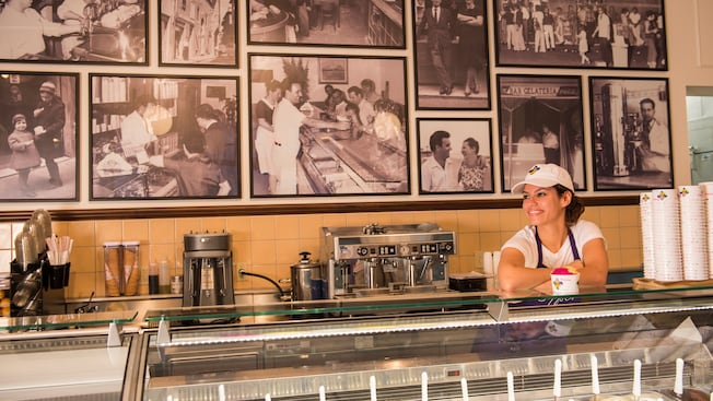 A female Cast Member stands behind a counter, ready to serve tasty gelato