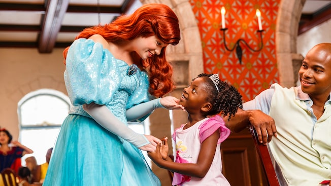 Princess Ariel greets a young girl dressed as Princess Aurora as her father looks on