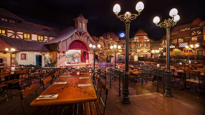 Bavaria-themed dining area in Biergarten Restaurant featuring long communal tables, street lamps and a stage