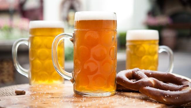 Pintas altas de cerveza helada servidas sobre una tabla de madera junto a pretzels salados estilo bávaro