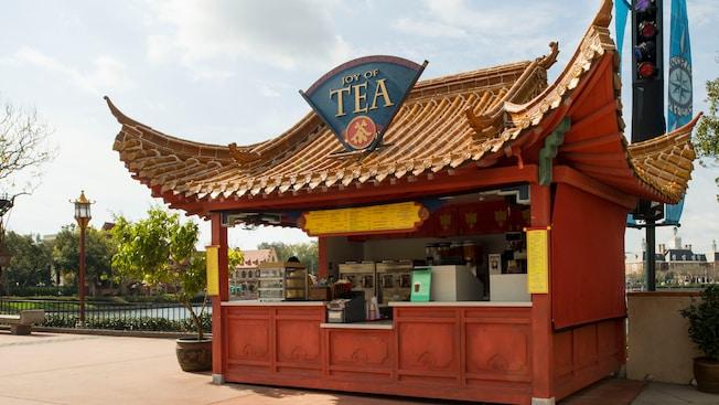 Quiosque externo com um amplo teto inspirado na arquitetura chinesa e uma placa que diz 'Joy of Tea' (Alegria do Chá)