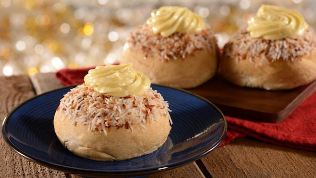 Three pastry buns topped with toasted coconut and vanilla cream