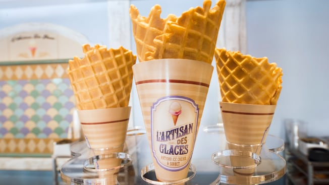 A trio of empty L'Artisan des Glaces waffle cones sits on the service counter