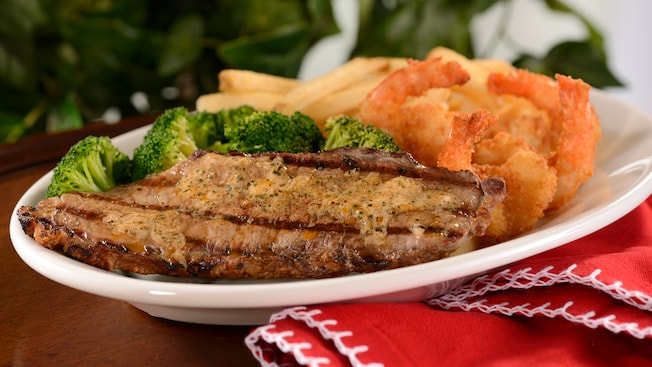 A grilled steak with a side of fried shrimp, French fries and broccoli