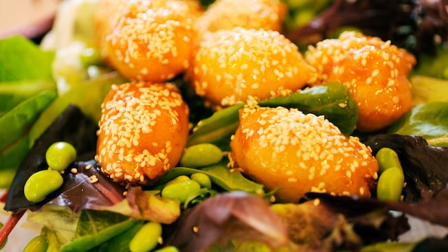Sesame chicken salad featuring orange chicken served atop a bed of leafy greens and edamame beans