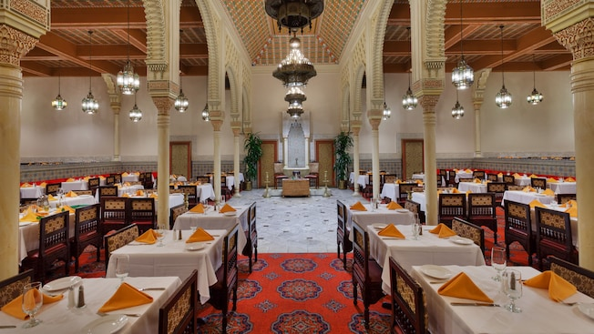 North African-themed dining room with a richly patterned carpet, white tablecloths, dark wood furniture and mosaic accents