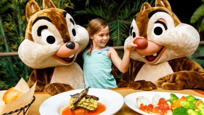 Una niña parada entre Chip 'n' Dale le aprieta a Dale la gran nariz roja, en el restaurante The Garden Grill