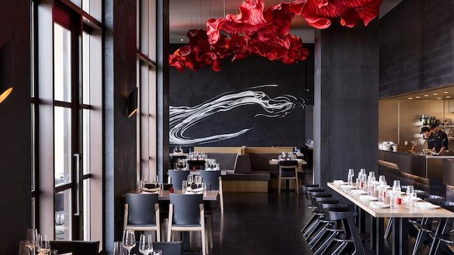 Salle à manger contemporaine décorée avec des tables de style moderne et cuisine ouverte avec les cuisiniers à l'œuvre