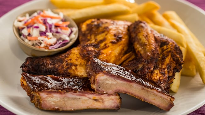 A plate with barbecue pork ribs and a quarter roasted chicken served with cole slaw and french fries