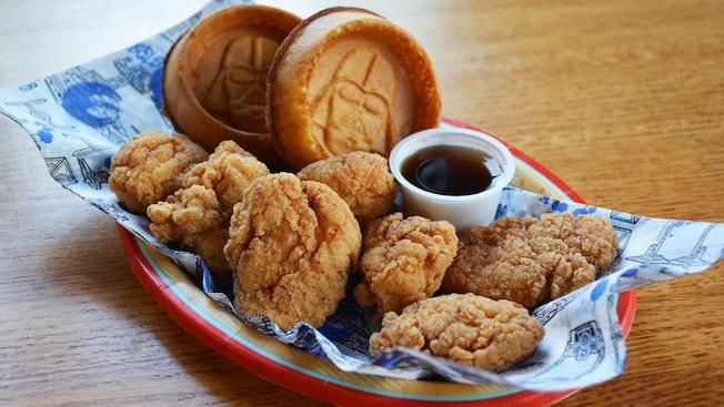 Une assiette remplie de filets de poulet frits, 2gaufres évoquant Dark Vador et un accompagnement de sirop d'érable