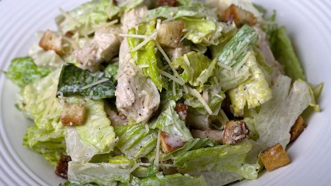 Una porción de ensalada Caesar con pollo, cubierta con queso parmesano, croutons y pimienta negra