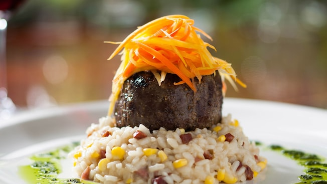 A finely plated filet of beef, topped with shaved carrots and set atop a serving of corn risotto