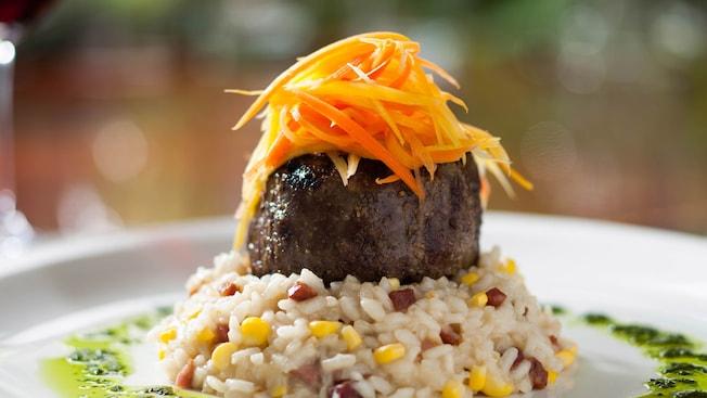 Um filé de carne bovina com apresentação fina, com cenoura ralada e uma porção de risoto de milho