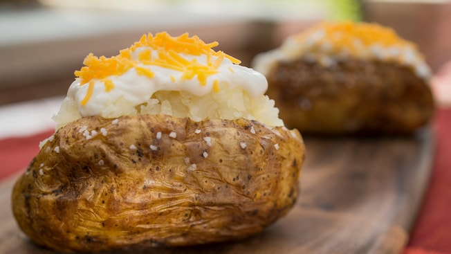 A freshly made baked potato topped with ample servings of sour cream, grated cheddar cheese and salt