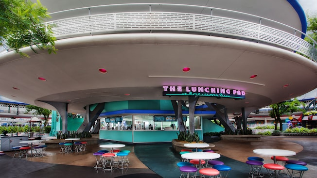 Mesas e bancos coloridos e uma placa de neon no lado de fora do restaurante The Lunching Pad na Tomorrowland