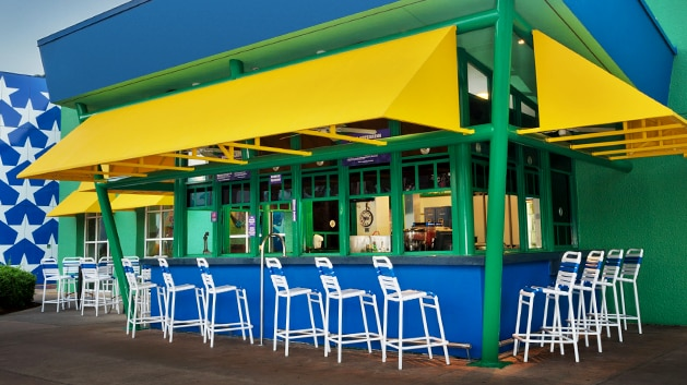 Tall deck chairs line the windows beneath a colorful banister at the Grandstand Spirits Pool Bar