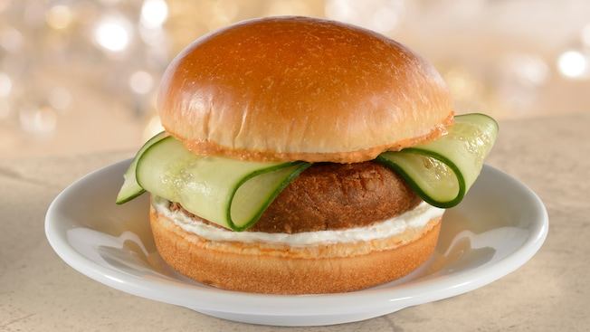 A falafel patty topped with cucumber slices, served between 2 buns