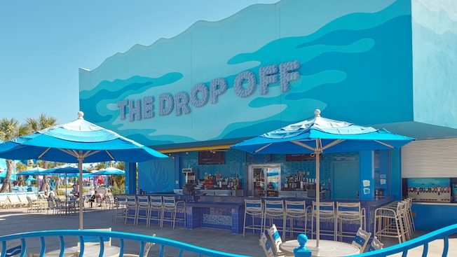 Mesas com guarda-sol e cadeiras perto do bar da piscina The Drop Off no Disney's Art of Animation Resort