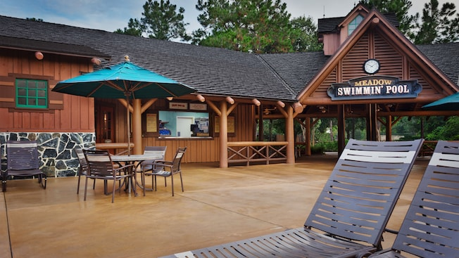 Sun loungers and umbrellaed table on a patio in front of Meadow Snack Bar