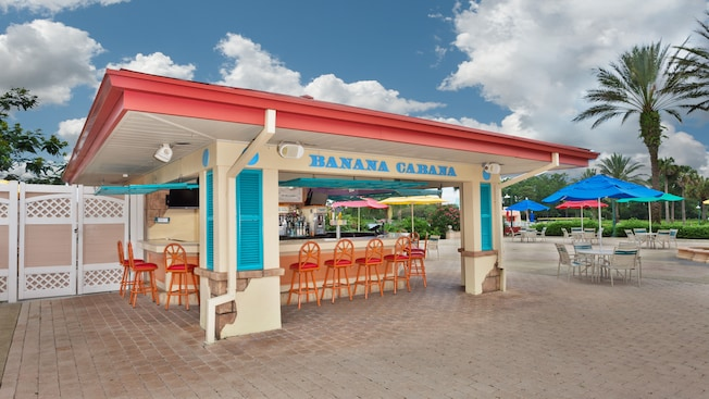 Orange bar stools surrounding a colorful, open-air cabana bar that sits close to the main pool