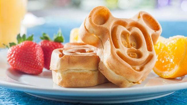 Un pedido de desayuno de waffles con forma de Mickey, fresas enteras y rebanadas de naranjas jugosas