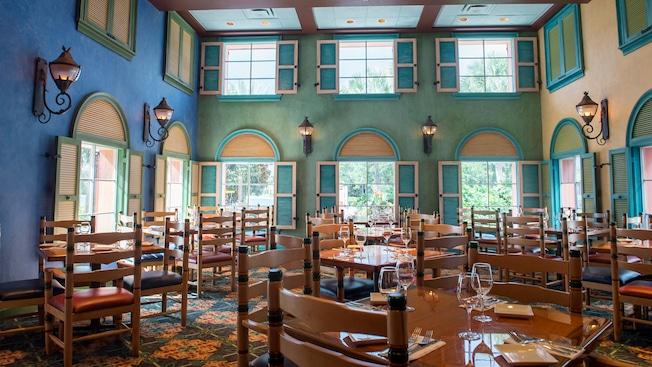 Postigos abiertos, faroles y grandes ventanas iluminando un comedor repleto de sillas y mesas