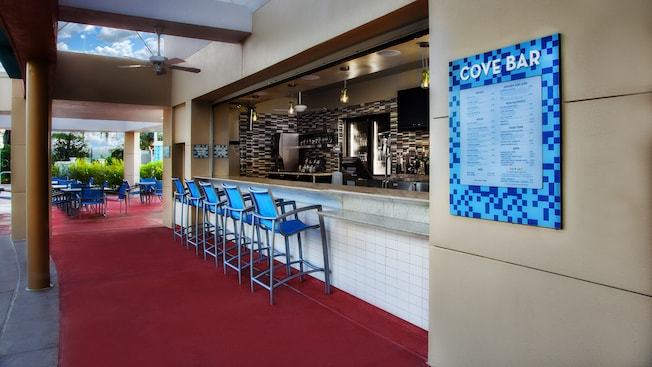 A row of blue chairs pulled up to the Cove Bar at Bay Lake Tower