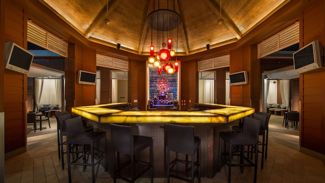 Light fixtures hang over an octagonal bar at the Cabana Bar and Beach Club