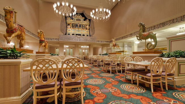 Whitewashed tables and chairs surrounded by carousel animals, with chandeliers overhead
